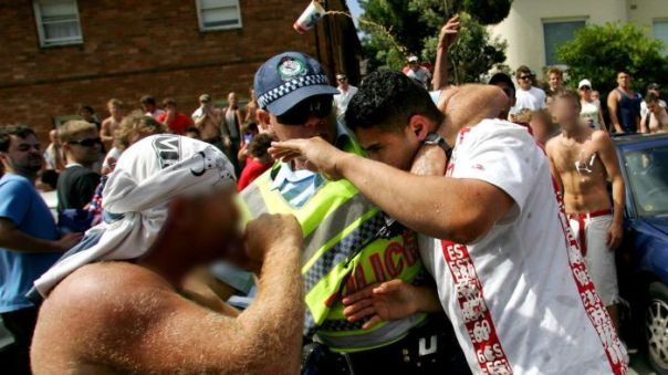 A police officer helps a man after he was set upon by a crowd at Cronulla beach in Sydney on December 11, 2005.