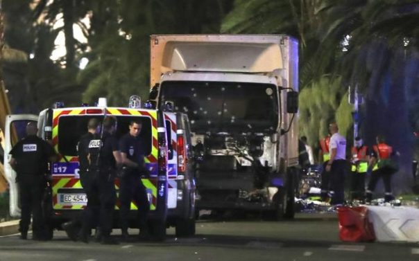 A devastated parent sits beside the body of a child run over by a semi-trailer driven by a crazed Islamic in Nice